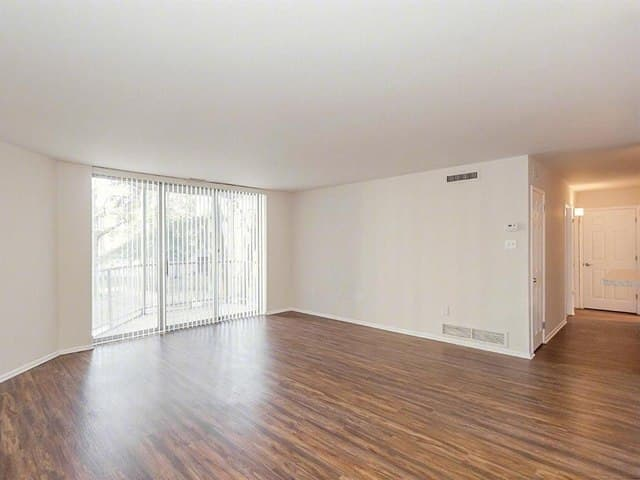 Spacious living space with hardwood floors at West River Apartments.