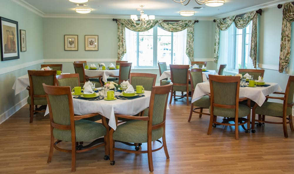 Dining hall with green accents at Artis Senior Living of Boca Raton in Boca Raton, Florida
