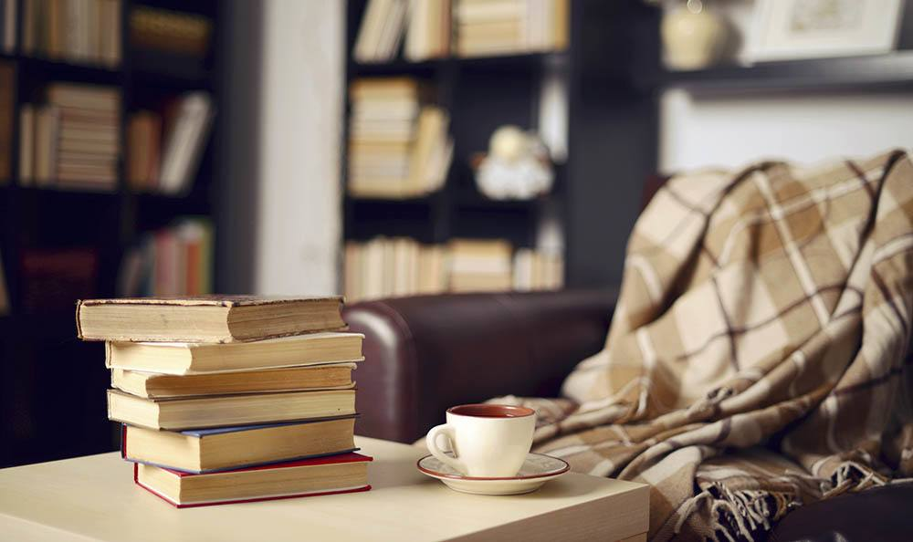 Books Stacked Near Armchair at Woodbrook Apartments in Indianapolis, IN