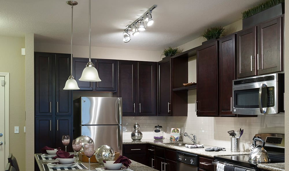 Apartment home's kitchen at Integra Cove showcasing dark wood cabinetry