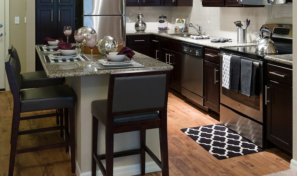 Apartment home's kitchen at Integra Cove showcasing stainless-steel appliances and hardwood floors