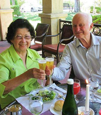 Residents toasting at a senior living community owned by Ray Stone Inc.