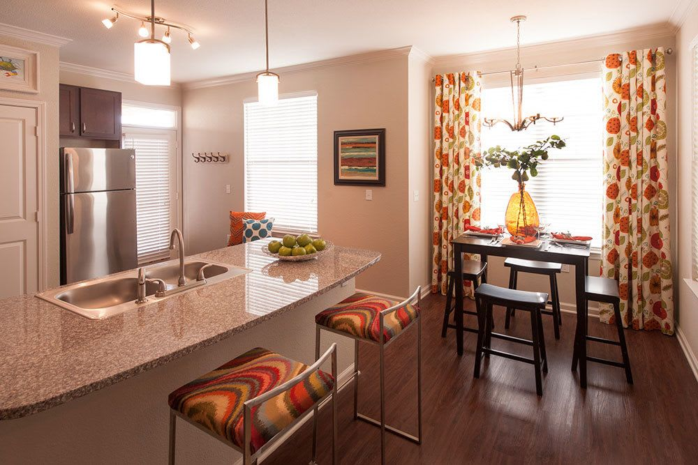 A view of the open kitchen and dining room inside one of the apartments at The Boulders on Fern Apartment Homes