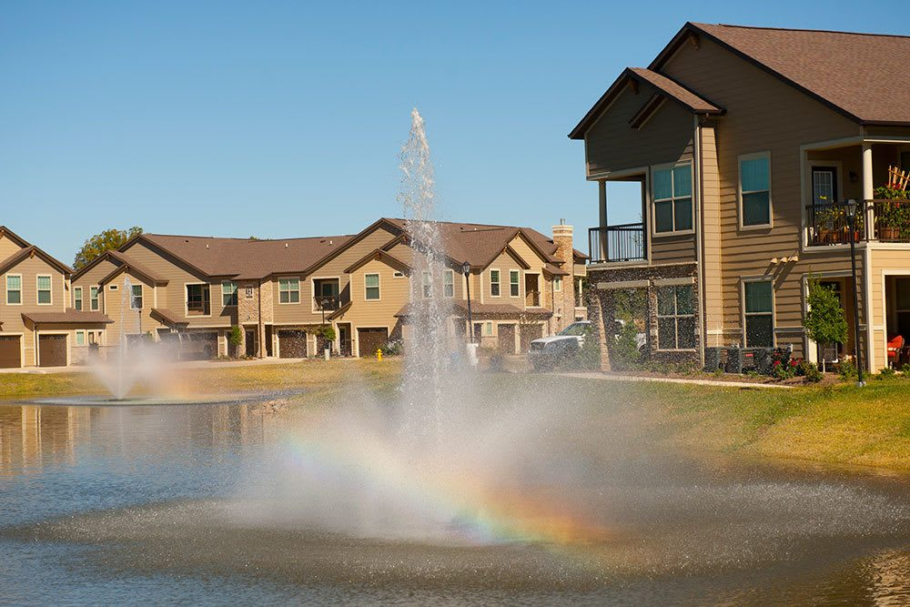 The community at The Boulders on Fern Apartment Homes features a man made lake and water feature