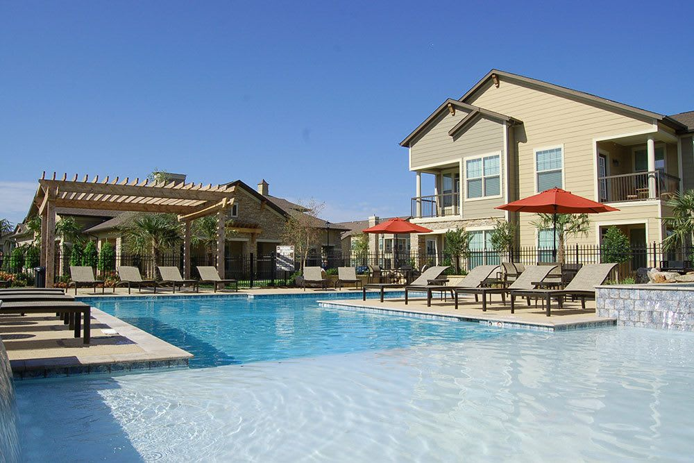 Relax in the saltwater swimming pool at The Boulders on Fern Apartment Homes to escape the heat