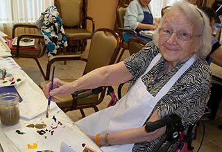Woman painting at memory care in Indianapolis
