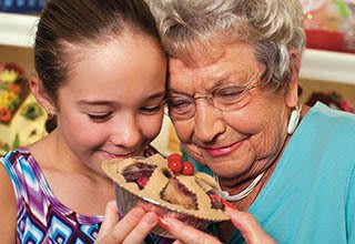 Grandmother and granddaughter share a pie