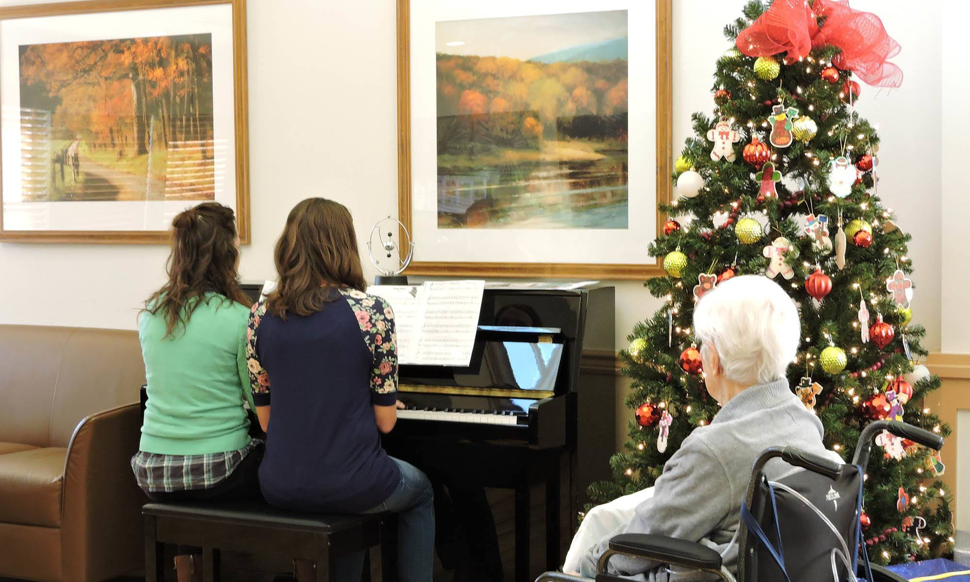 Residents listening to a piano piece at Harvester Place