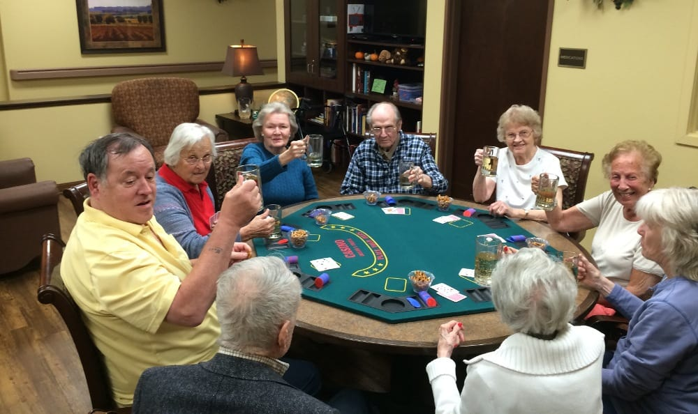 Happy residents playing cards at our senior living facility in Littleton