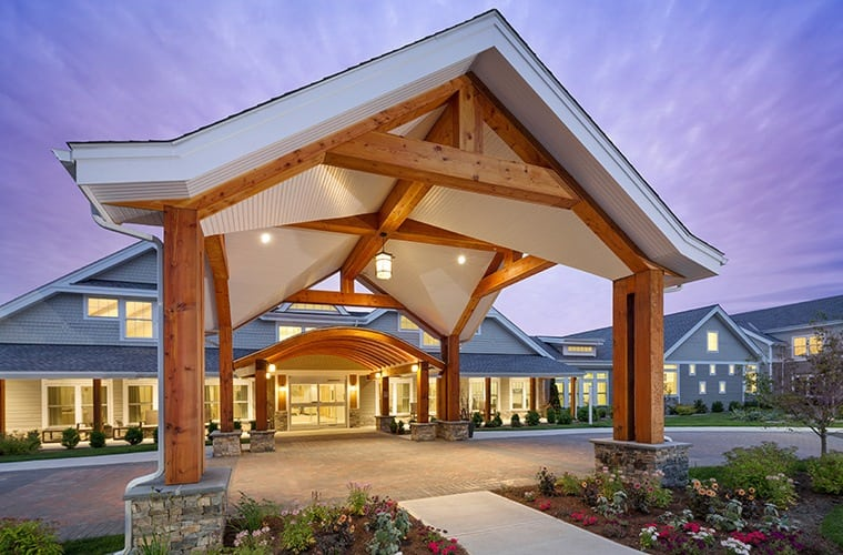 Grand wood-beamed archway as you approach the entrance at one of our Maplewood Senior Living communities.