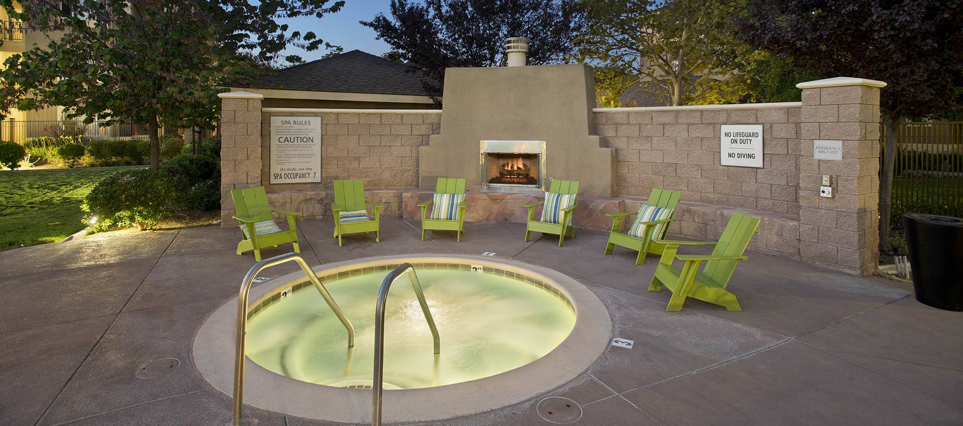 Spa with seating by fireplace at Cross Pointe Apartment Homes in Antioch