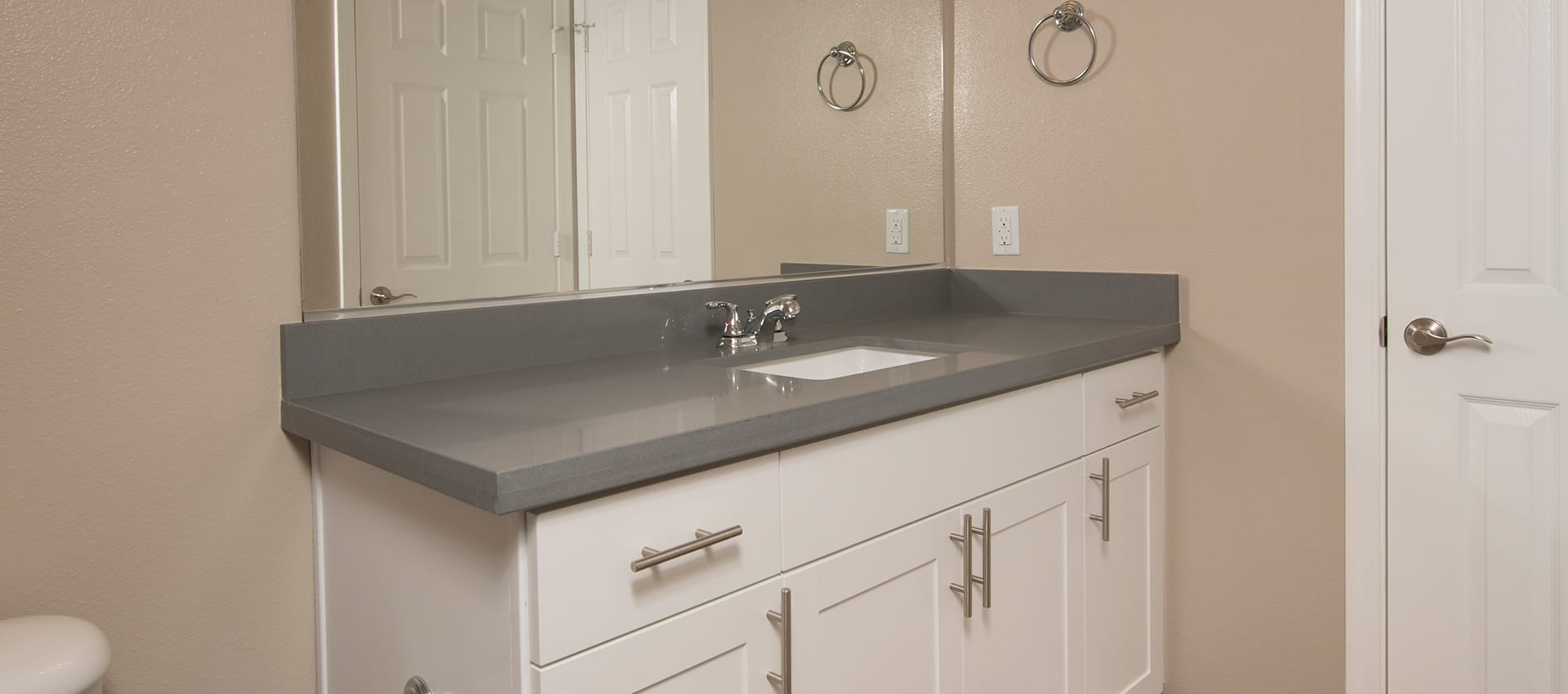 Kitchen sink with white cabinetry at Esplanade Apartment Homes in Riverside, California