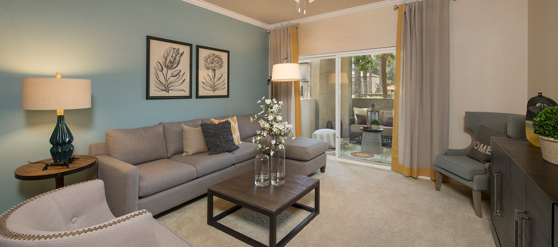 Spacious living room with sliding glass door at Esplanade Apartment Homes in Riverside, California