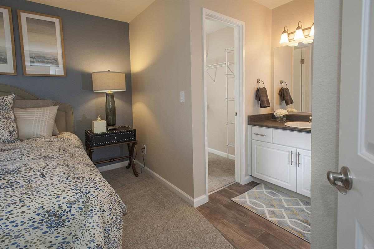 Cozy master bedroom with ensuite bathroom at Mill Springs Park Apartment Homes in Livermore, California
