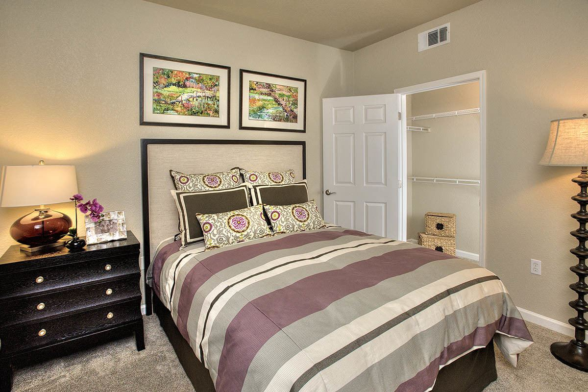 Cozy bedroom with closet racks at River Oaks Apartment Homes in Vacaville, California