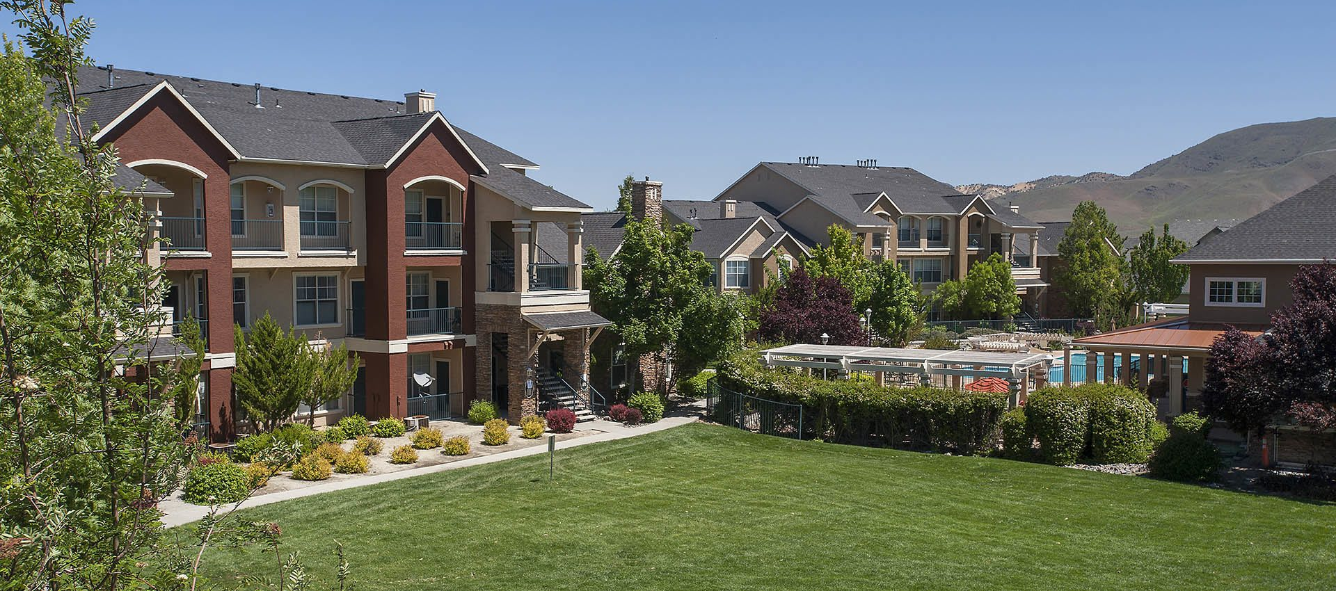 Condominiums with easy access to grass field at The Vintage at South Meadows Condominium Rentals in Reno