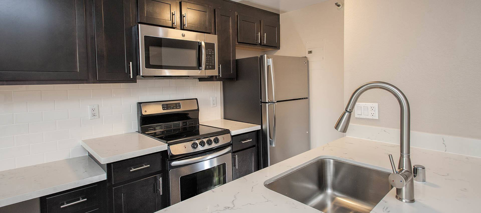Luxury Kitchen With Dark Wood Cabinets at Tower 737 Condominium Rentals in San Francisco