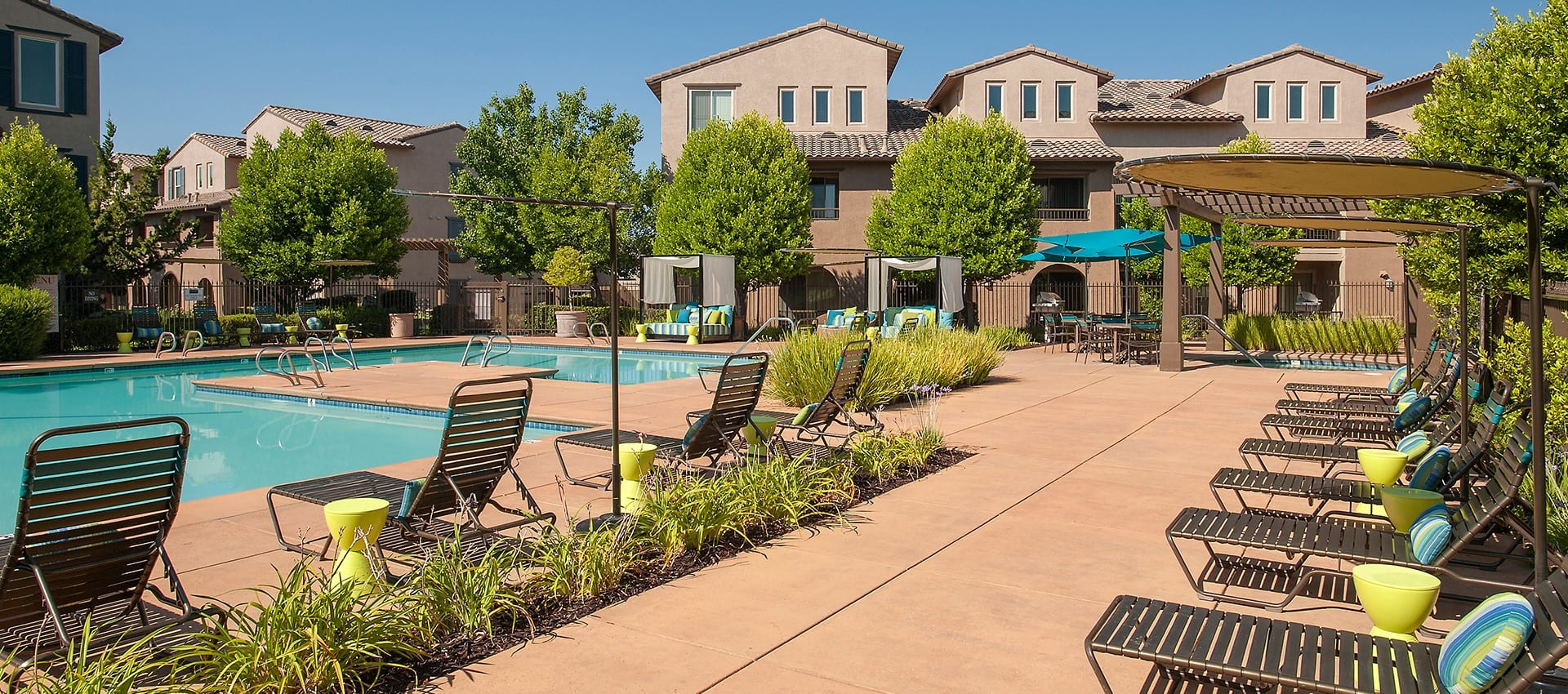 Sun deck next to the swimming pool at Venu at Galleria Condominium Rentals in Roseville, California