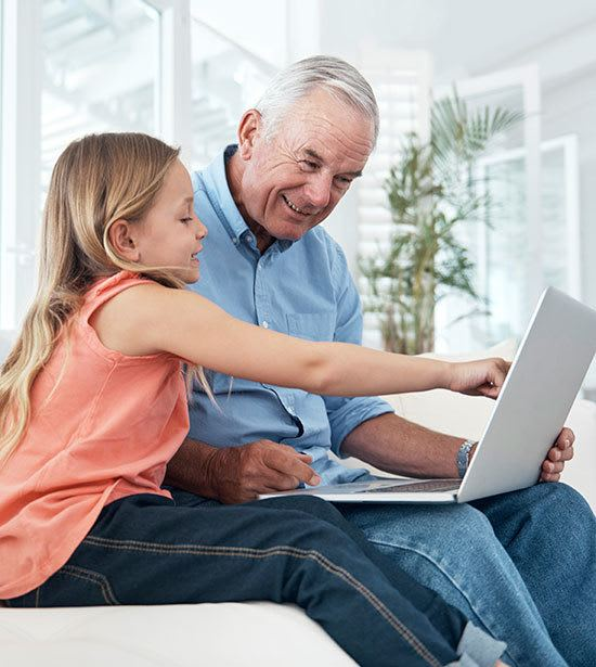 A senior living resident at Cedarbrook of Rochester and his granddaughter doing research on the computer