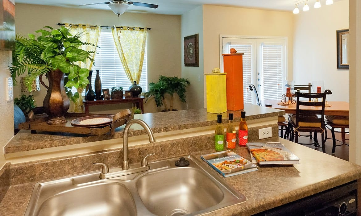 The breakfast bar is the perfect spot for your friends to watch you cook in your new kitchen at Arioso Apartments in Grand Prairie, TX.