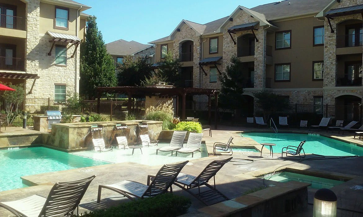 The swimming pool area at Arioso Apartments in Grand Prairie, TX has plenty of room - both inside and out of the water.