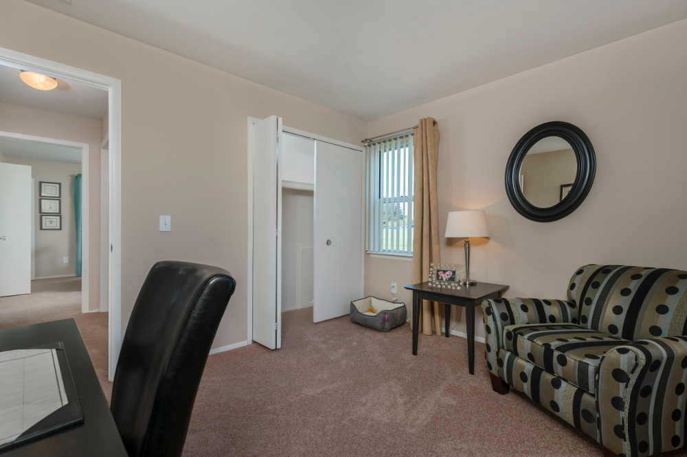 Closet and cozy couch at Clinton Place Apartments in Clinton Township, MI
