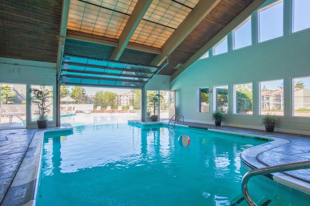 Indoor and outdoor pool at The Pines of Cloverlane Apartments in Michigan