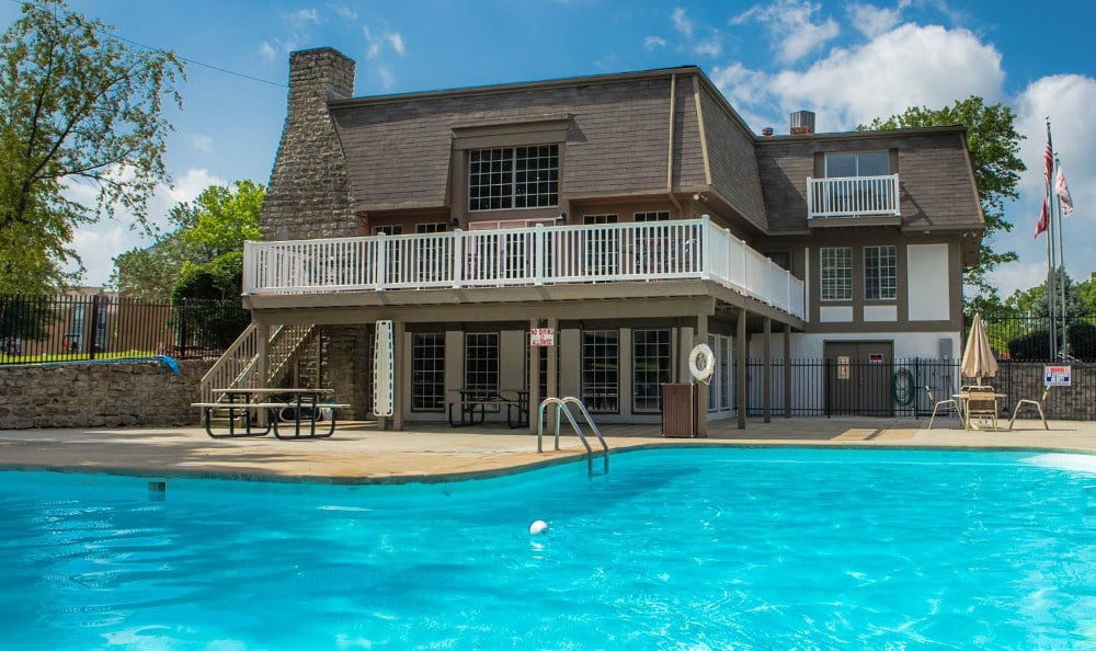 The exterior of the community clubhouse and the pool at Camelot East Apartments in Fairfield, OH