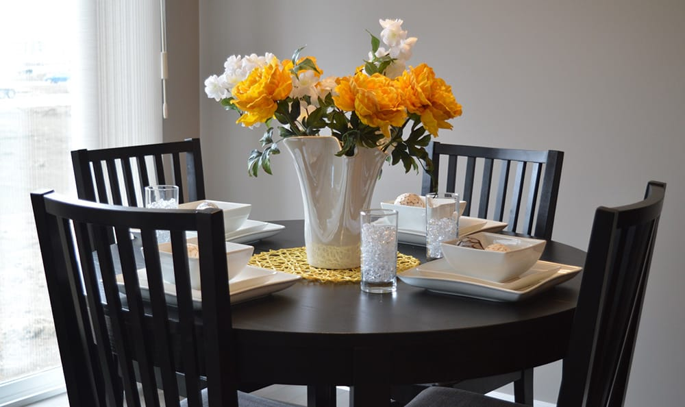 Dining room table decorated with flowers at 1010 Pacific Apartments