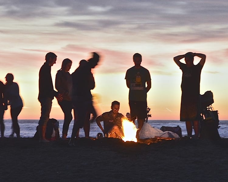 Friends and neighbors enjoying a bonfire on the beach near Pacific Shores apartments