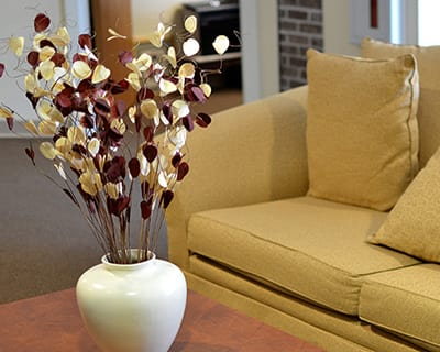 A decorative vase compliments a neutral toned couch at Gardenview