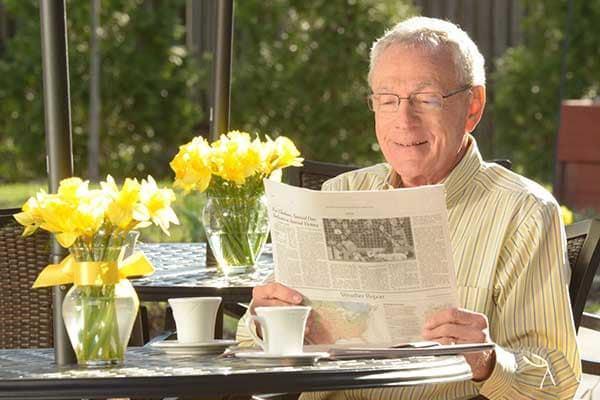 A gentleman catches up on local news while reading the newspaper at Symphony at Delray Beach in Delray Beach, Florida
