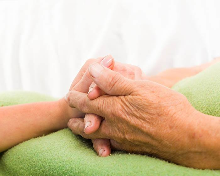 Parkinson's care patient holding hands at Skyline Place Senior Living