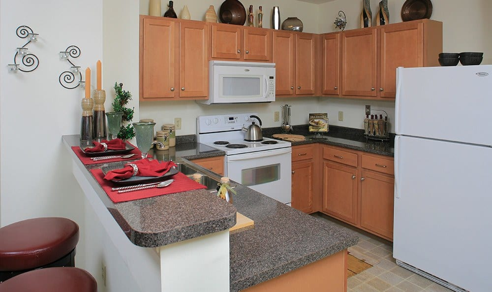 A modern kitchen with granite countertops and contemporary finishes at Kimball Towers at Burlington.