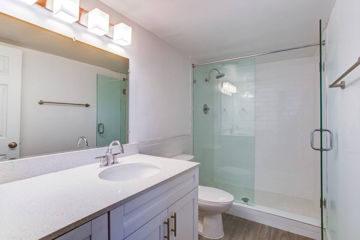 Bright and modern bathroom with plenty of countertop space in model home at Aliro Apartments in North Miami, FL