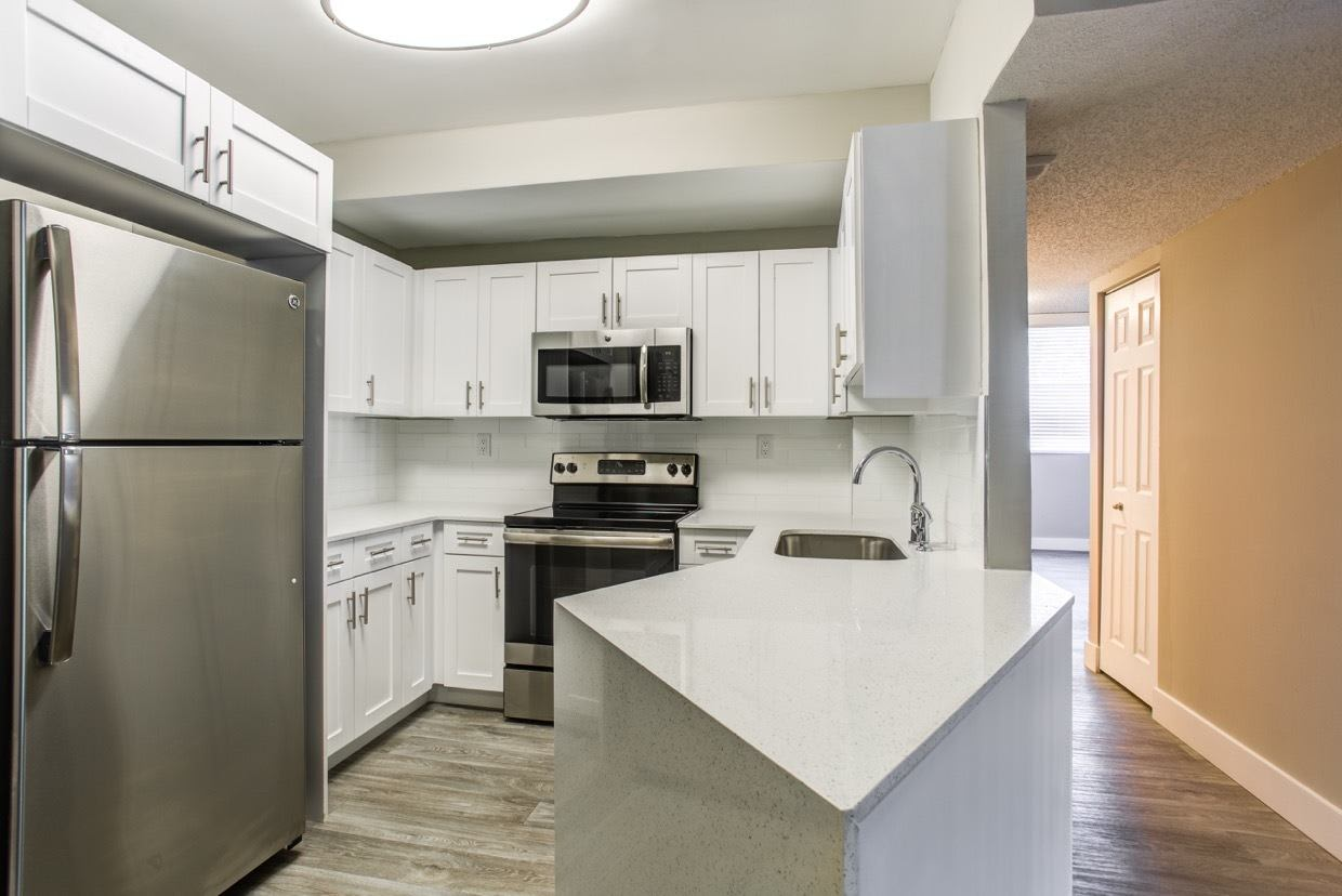 Kitchen with stainless-steel appliances and white cabinetry in model home at Aliro Apartments in North Miami, FL