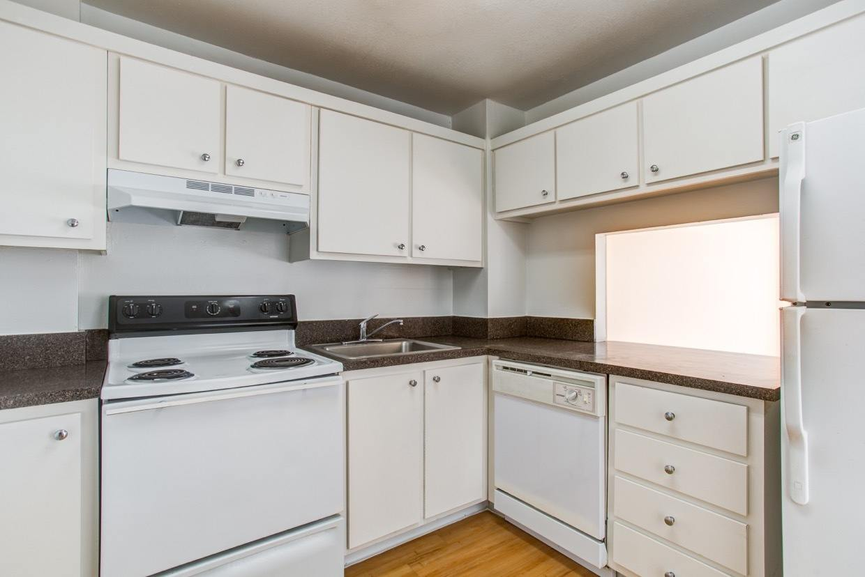 White appliances and hardwood floors in model home's kitchen at Aliro Apartments in North Miami, FL