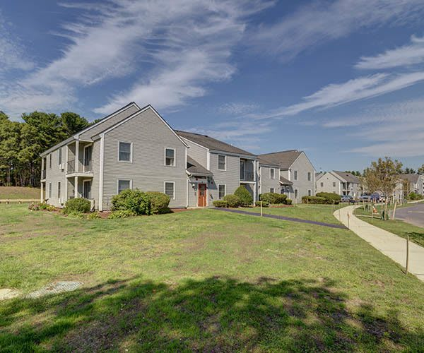 Building Exterior And Grassy Yard at The Oak at Island Creek Village in Duxbury