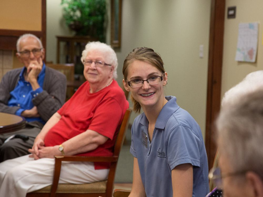 A new care-giver spending time with residents at The Heritage at Meridian Gardens