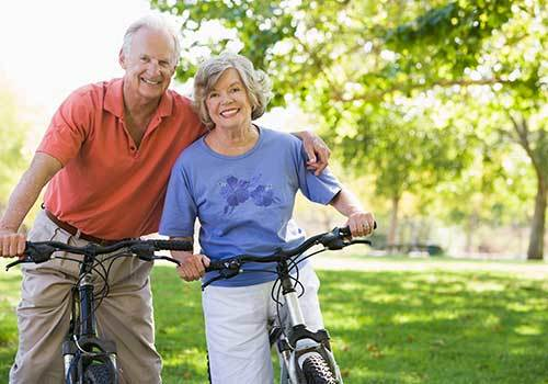 Couple staying healthy and riding their bicycles at Osmond Senior Living in Lindon in Utah.