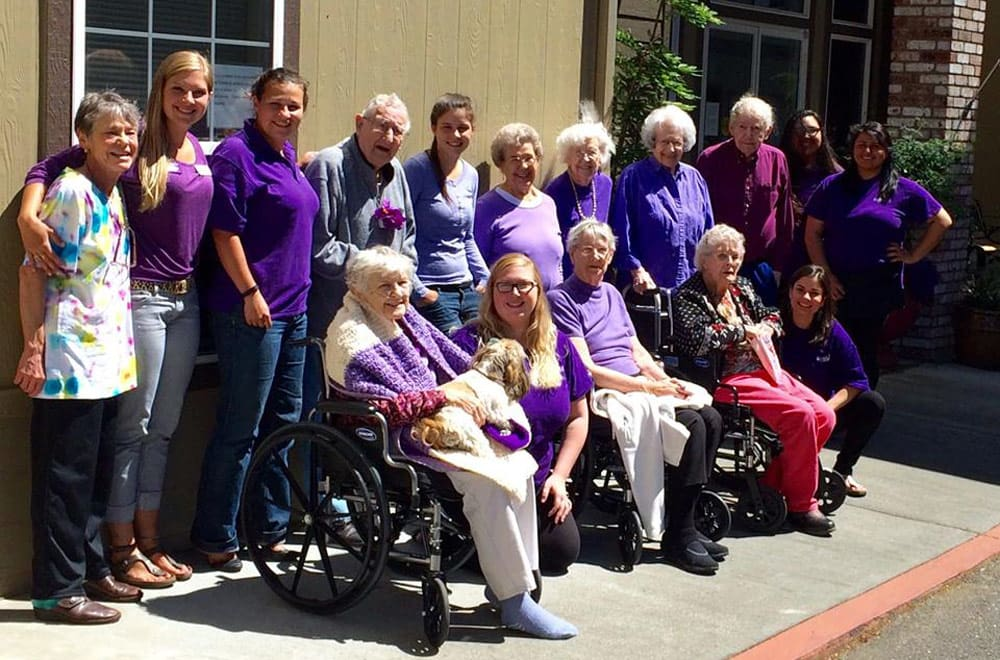 Senior residents and staff smiling for a group photo
