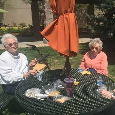 Residents having a snack outside at Garden Square of Greeley Assisted Living and Memory Care.