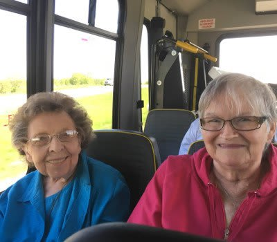 Women socializing on a bus going to Marla Vista Assisted Living and Memory Care