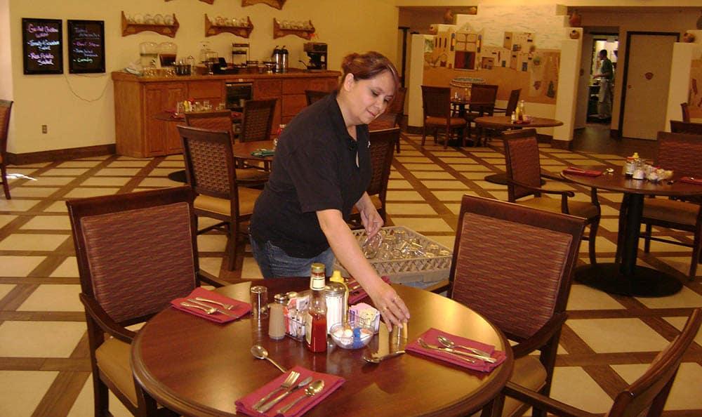 Team member setting table at senior living in Las Cruces