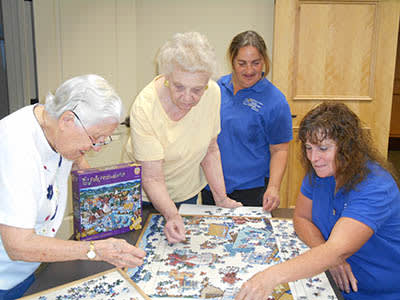 Residents of Majestic Rim Retirement Living enjoy a puzzle