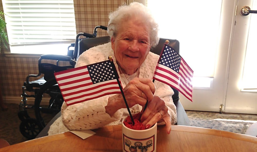 Woman with flags at Sundial Assisted Living
