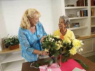 Senior living residents in Maryland arrange flowers together.