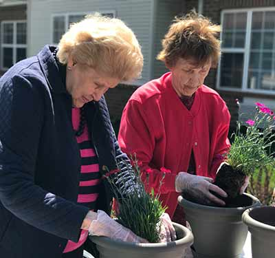 Senior living residents gardening at Waltonwood Lake Boone