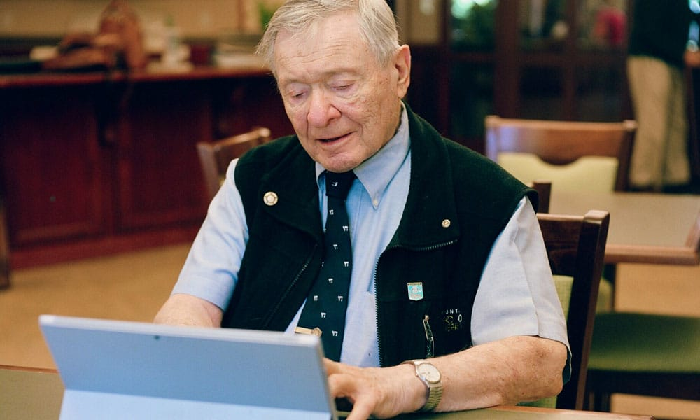 Resident enjoying time on his laptop at Merrill Gardens at Solivita Marketplace