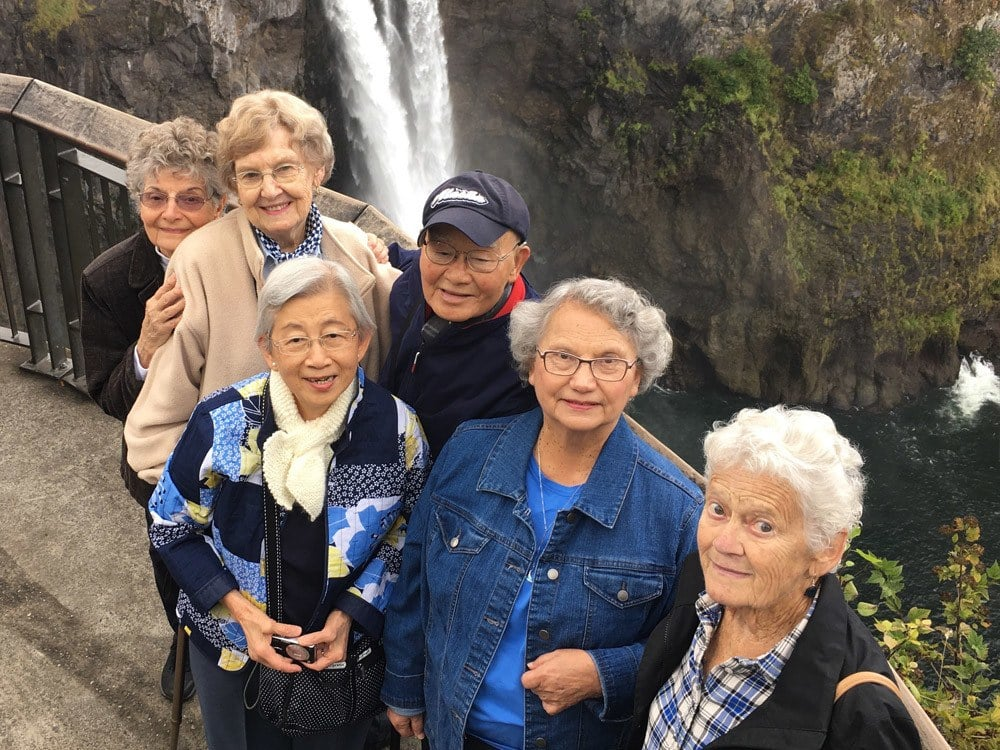 Group of Merrill Gardens at The University residents at waterfall
